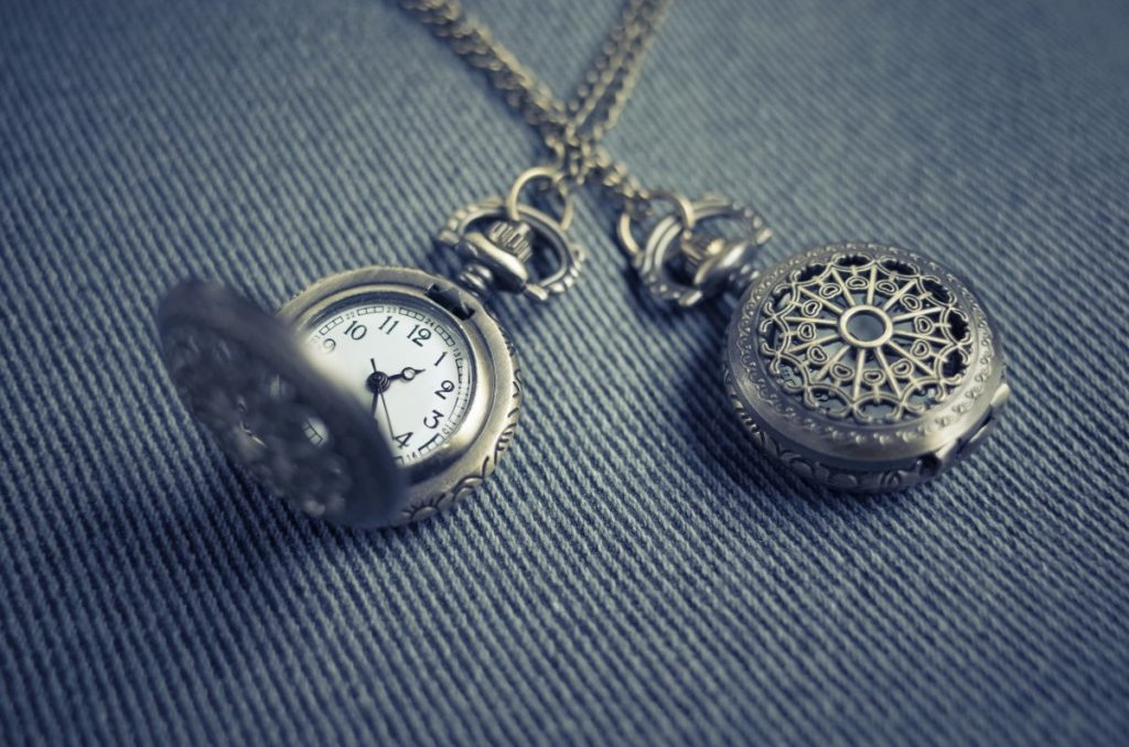 A round pendant necklace with a clock inside