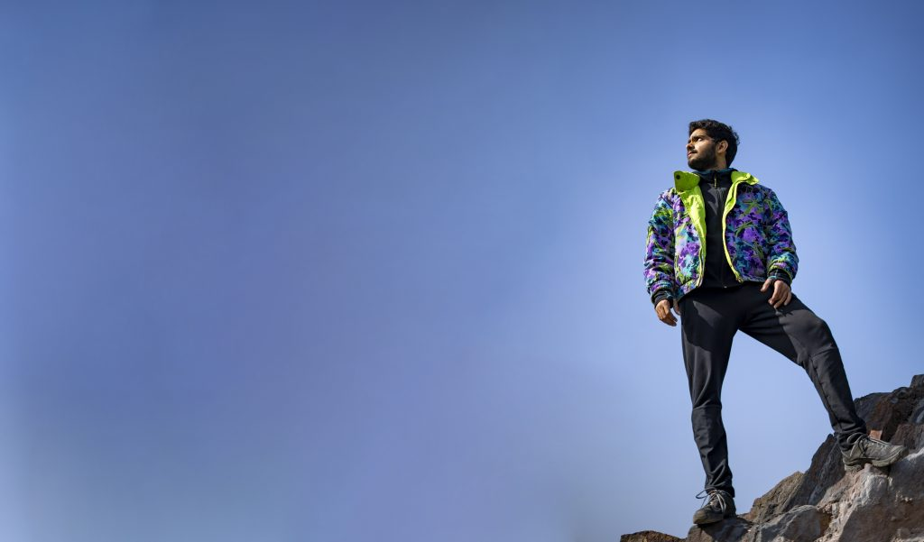 Banner image of a Young Indian boy standing on the top of cliff wearing a snow jacket and track pants. Enjoying and freedom concept.